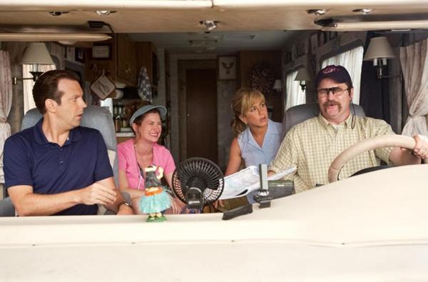 David e Rose (ambos de azul) assumem papéis de pai e mãe para buscar um carregamento de drogas (Warner Bros/Divulgação)