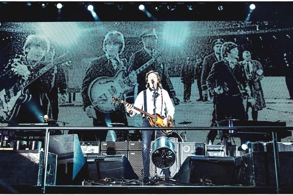 Paul McCartney durante o show em Candlestick Park. Atrás uma das fotos do último show dos Beatles (Paul McCartney/Facebook/Reprodução)