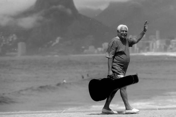 Imagem do músico Dorival Caymmi, com case de violão, caminhando na orla da praia, exibida na exposição Caymmi 100 anos, em cartaz no Museu dos Correios (ArquivoPessoal)