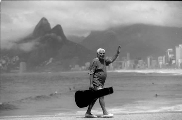 Imagem do músico Dorival Caymmi, com case de violão, caminhando na orla da praia, exibida na exposição Caymmi 100 anos, em cartaz no Museu dos Correios (Arquivo Pessoal)