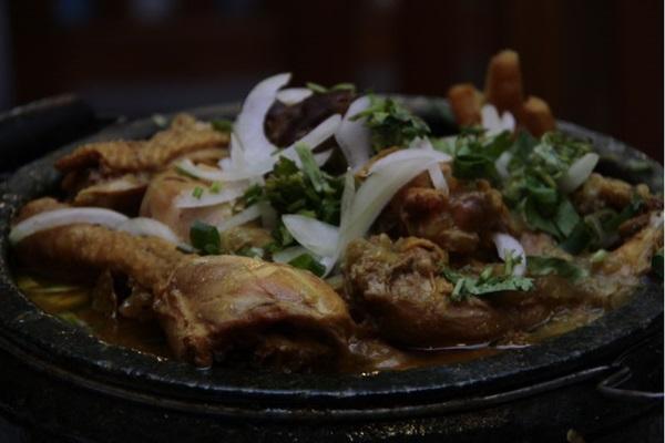 O gerente, Cláudio de Castro, e a galinha caipira do Santana, no menu há 30 anos  (Ana Rayssa/Esp. CB/D.A Press)