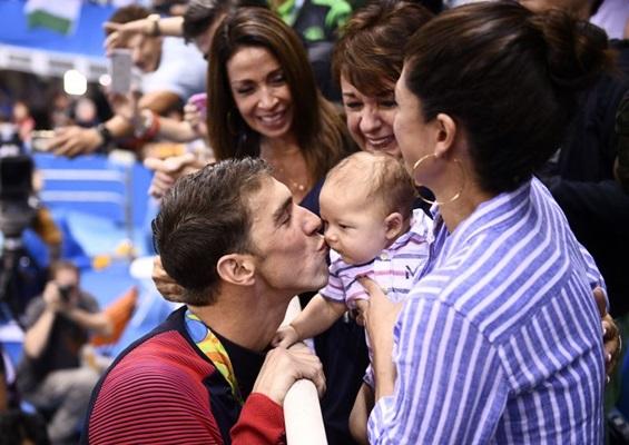 Michael Phelps beija seu filho Boomer  (AFP PHOTO / Martin BUREAU)
