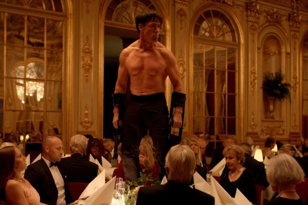 Performance de artista para patrocinadores é ponto alto do filme (Dominic West/Terry Notary)
