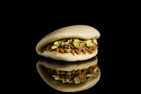 O pão chinês bun é levemente adocicado e feito no vapor. Ele vai à mesa com o recheio de carne suína (Koni/Divulgação)